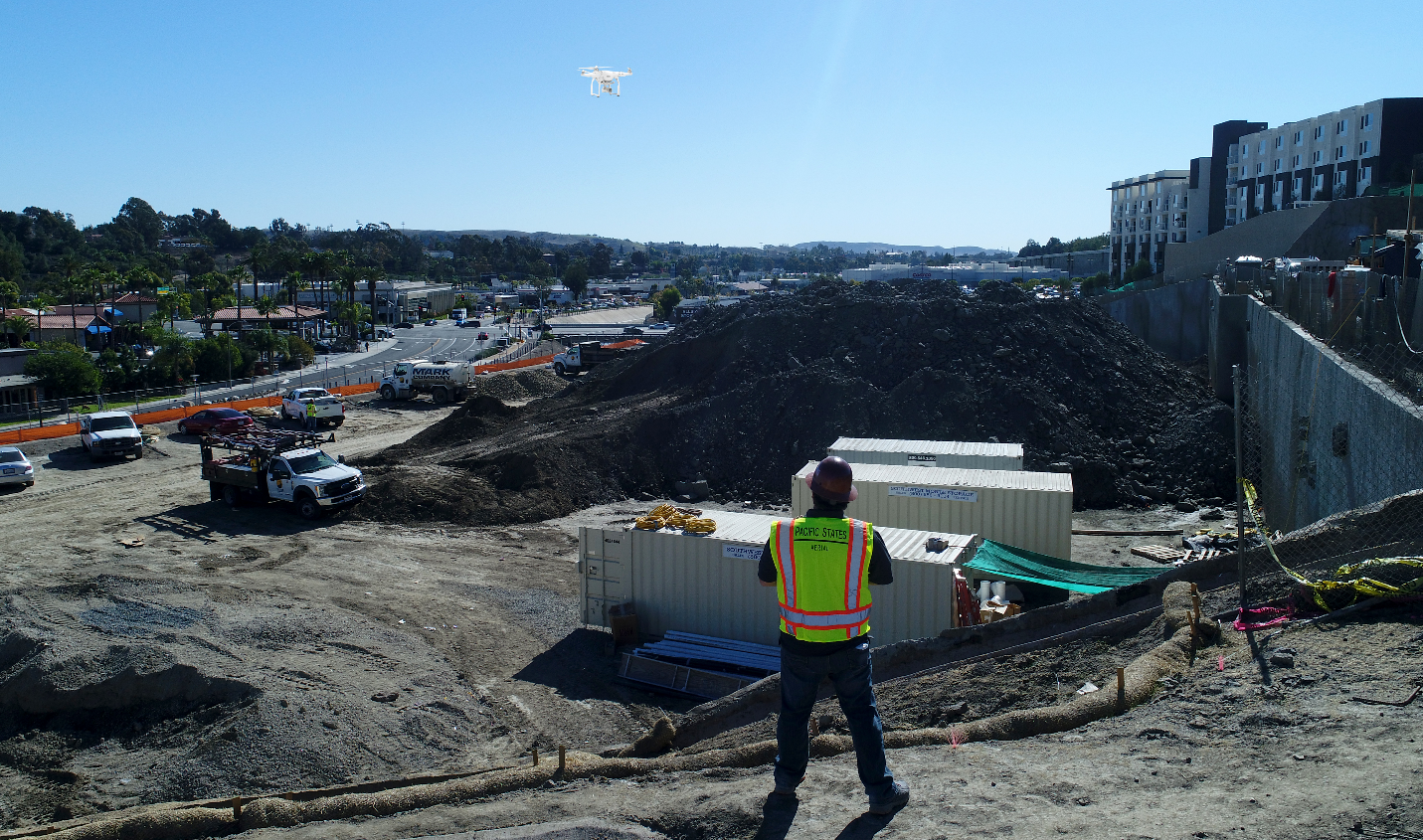 drone pilot flying drone over a stock pile at a construction site