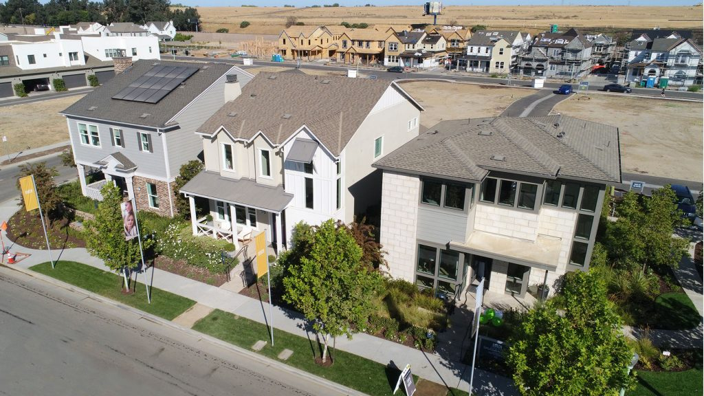 aerial view of new construction homes in foreground with more homes at various stages of construction in background