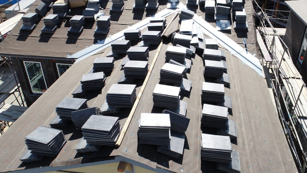aerial closeup of unfinished roof with stacks of tile all over, used for safe and effective inspections of hard to access areas