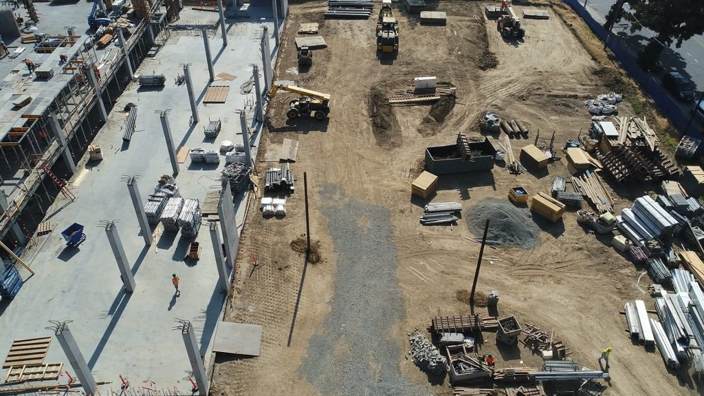 aerial view of a construction site with stockpiles, other materials, workers and equipment scattered throughout the area
